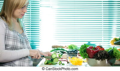 Pregnant woman chopping cucumber