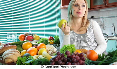 Pregnant woman eating apple near a lot of vegetables and...