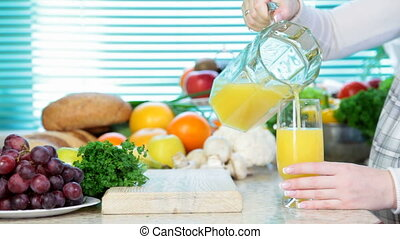 pouring orange juice - Female hand pouring orange juice in...
