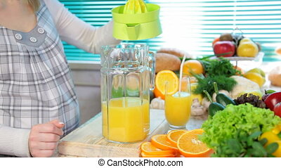 fresh orange juice - Female hand squeezes orange juice on a...
