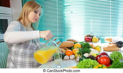 Pregnant woman pouring orange juice in the kitchen near a...