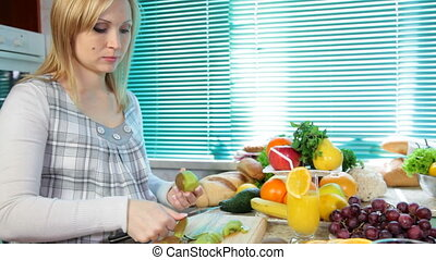 Pregnant woman preparing fruit salad slicing kiwi