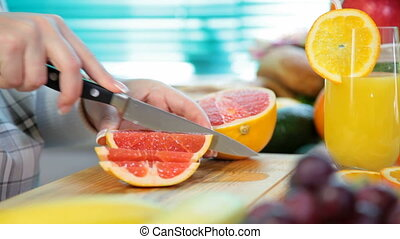 Woman hands cutting grapefruit in the kitchen