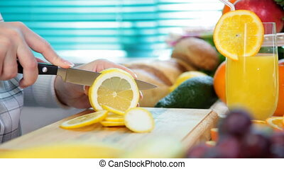 Women hands sliced lemon