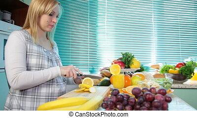 Pregnant woman cutting lemon