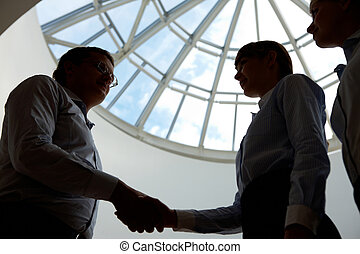 Consensus - Outlines of business people handshaking after...