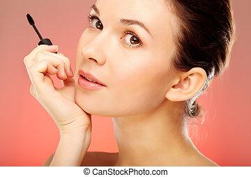 Coquette - Portrait of pretty female with mascara brush...