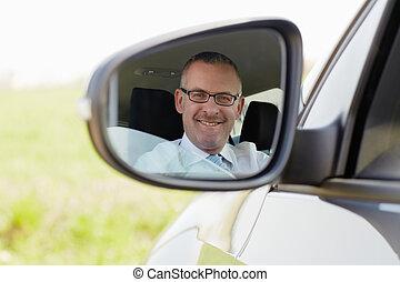 businessman in car smiling at camera