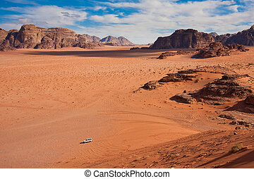White car in a Wadi Rum desert, Jordan - Small car in a huge...
