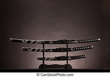 Three ancient japanese swords with a monochrome lighting...