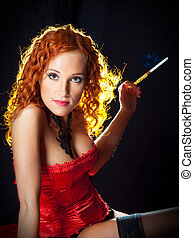 Sexy girl with red hair wearing red corset holding amber mouthpiece on black