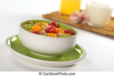Fresh and healthy breakfast: Fruit salad out of mango, strawberry and white grape with puffed wheat cereal and orange juice and milk in the background (Selective Focus, Focus on the middle of the bowl