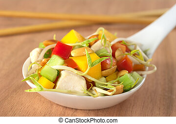 Fresh Asian salad with chicken, mango, cucumber, bean sprouts, red bell pepper and peanuts on white ceramic spoon with wooden chopsticks in the back (Selective Focus, Focus on the front of the food)