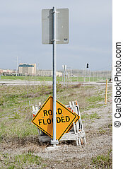 Road flooded sign and barricade sawhorses leaning against...