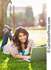 Asian student on campus - A shot of an asian student using...