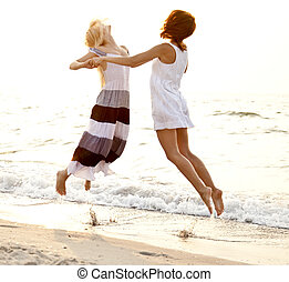 Two beautiful young girlfriends jumping on the beach at...