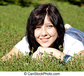 Portrait of beautiful brunette girl with blue eyes on green grass in the park.