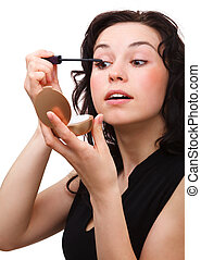 Woman is applying mascara while looking in mirror - Young...