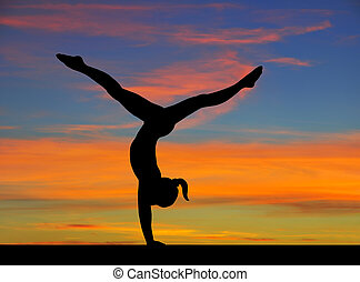 Gymnastics sky - Silhouette of a gymnast girl in balance on...