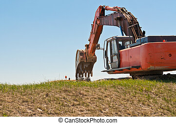 Hydraulic Excavator at Work - A hydraulic excavator scoops...