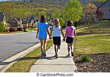Three Young Girls Walking - Three young girls going up a...