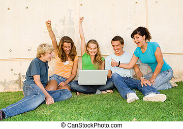 group of teens with laptop hands raised for success or...