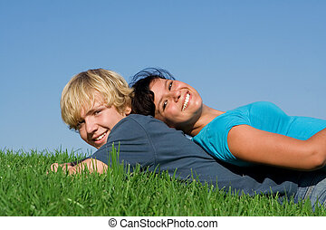 happy smiling, teen couple laying on grass in summer