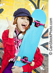 Closeup portrait of a happy young girl with skateboard and...