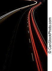 Cars moving fast on a night highway motion blurred image
