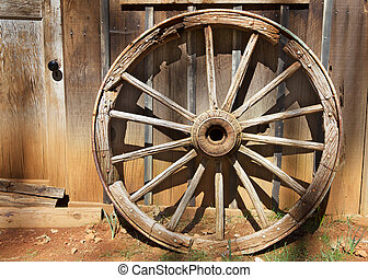 Old Wagonwheel  in strong sunlight against a barn wall