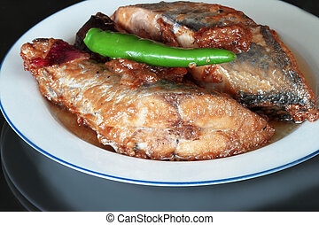 Fried fish with coconut milk in a white plate