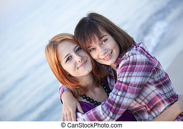 Closeup portrait of two happy girls on the beach
