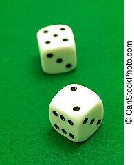 Die - White die isolated against a green velt