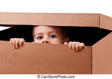 Boy peeping over a brown cardboard box