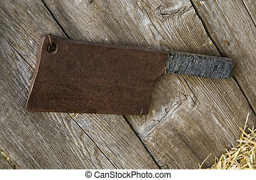 Old rusty meat cleaver hanging on a wall.