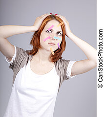 Confused red-haired businesswomen with notes on face.