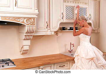 Bride in a luxury dress stands in the kitchen