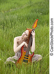 Girl with guitar at field