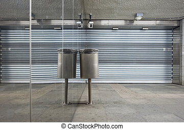 Trash can and closed store front shutters along a mirror...