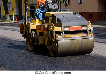 road roller with construction worker on bitumen road