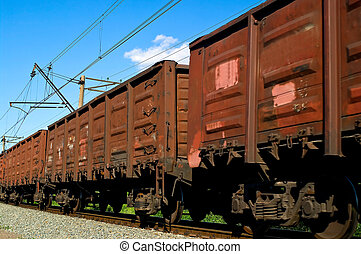 Rusty brown freight cars passing over a grade crossing...