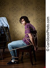 Tied young man - An image of a young man tied on a chair