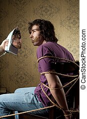 Torture - An image of a bound man on a chair and iron