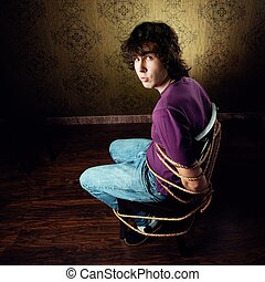 Prisoner - An image of a young man on a chair