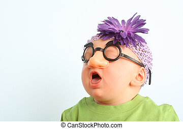 Funny baby wearing toy glasses and headband