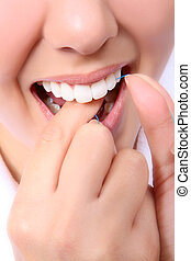 Woman Flossing Her Teeth - A cose-up of a woman flossing her...