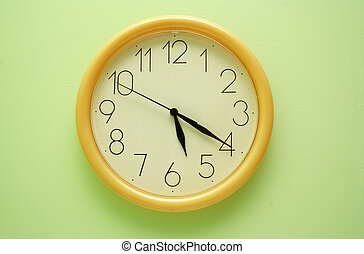 Yellow wall clock on the green