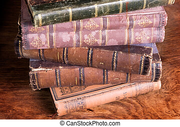 stack of antique books backs on aged wooden background taken...