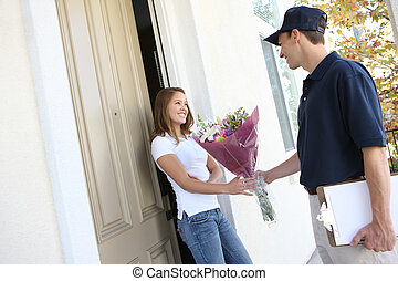 Pretty Woman Receiving Flowers - A delivery man giving...