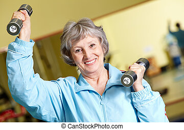 Exercise with barbells - Portrait of aged woman doing...